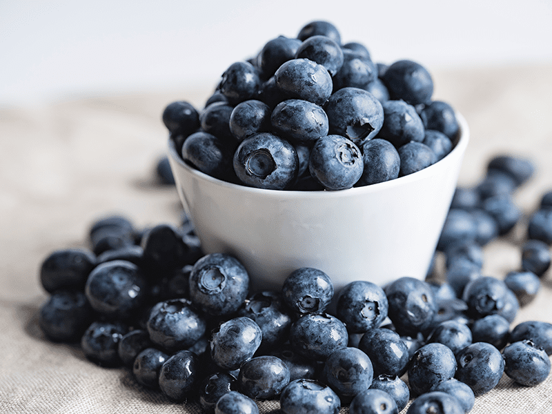 How does crowdfunding work? A bowl of blueberries overflowing to represent overfunding.